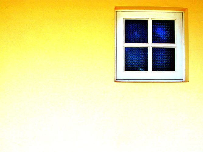 Four blue, square panes of glass in a white, wooden window frame on a bright yellow wall.